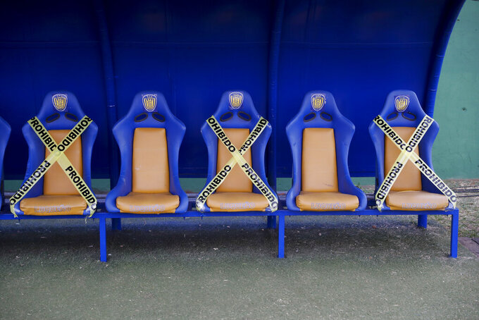 Sportivo Luqueno's bench is marked with caution tape to help players maintain a safe social distance at the Feliciano Caceres stadium prior to a local championship match against Sportivo Luqueno and Cerro Porteno, in Luque, Paraguay, Friday, Aug. 7, 2020, amid the new coronavirus pandemic. (AP Photo/Jorge Saenz)