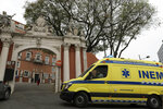 An ambulance enters the Sao Jose Hospital in Lisbon, Monday, March 29, 2021. An Italian fugitive, convicted in his homeland of ordering the revenge killing of a mobster's wife, was arrested in Portugal on Monday in a clinic where he was reportedly being treated for COVID-19. (AP Photo/Pedro Rocha)