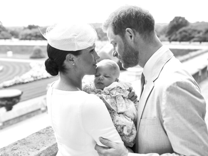 This is an official christening photo released by the Duke and Duchess of Sussex on Saturday, July 6, 2019, showing Britain's Prince Harry, right and Meghan, the Duchess of Sussex with their son  Archie Harrison Mountbatten-Windsor at Windsor Castle with with the Rose Garden in the background, in Windsor, England. (Chris Allerton/©SussexRoyal via AP)