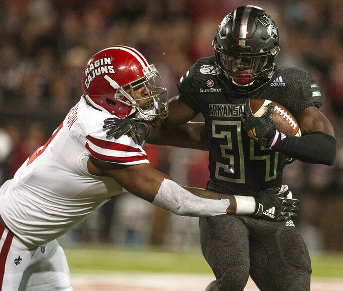 Arkansas State running back Marcel Murray (34) runs with the ball before getting tackled by Louisiana-Lafayette defender Kendall Wilkerson (8) during the first half of an NCAA college football game Thursday, Oct. 17, 2019, in Jonesboro, Ark. (Quentin Winstine/The Sun via AP)
