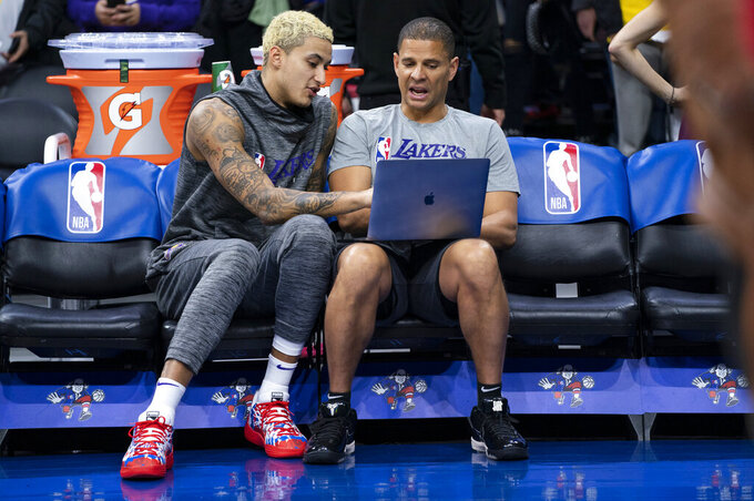 FILE - In this Jan. 25, 2020, file photo, Los Angeles Lakers' Kyle Kuzma, left, looks over the computer with assistant coach Miles Simon, right, prior to the first half of an NBA basketball game against the Philadelphia 76ers in Philadelphia. Former Arizona All-America guard Miles Simon scored 30 points to help Arizona defeat Kentucky in the 1997 NCAA college basketball championship game. (AP Photo/Chris Szagola, Fle)