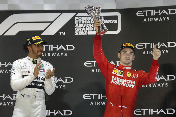 Second place Ferrari driver Charles Leclerc of Monaco, right, celebrates on the podium with Mercedes driver Lewis Hamilton of Britain after the Emirates Formula One Grand Prix, at the Yas Marina racetrack in Abu Dhabi, United Arab Emirates, Sunday, Dec.1, 2019. (AP Photo/Hassan Ammar)