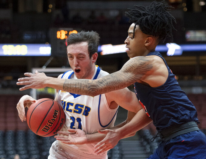 UC Santa Barbara guard Max Heidegger, left, drives toward the basket as Cal State Fullerton guard Kyle Allman Jr. defends during the first half of an NCAA college basketball game at the Big West men's tournament in Anaheim, Calif., Friday, March 15, 2019. (AP Photo/Kyusung Gong)