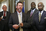Former Republican House Speaker Kris Steele, center, the executive director of Oklahomans for Criminal Justice Reform, speaks after a group working to reduce Oklahoma's prison population launched an initiative petition that could lead to the release of hundreds more inmates, Tuesday, Nov. 12, 2019, in Oklahoma City. (AP Photo/Sue Ogrocki)