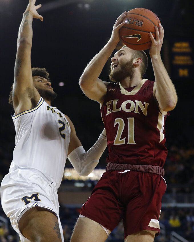 Elon guard Andy Pack (21) prepares to shoot as Michigan forward Isaiah Livers (2) defends during the first half of an NCAA college basketball game Friday, Nov. 15, 2019, in Ann Arbor, Mich. (AP Photo/Carlos Osorio)