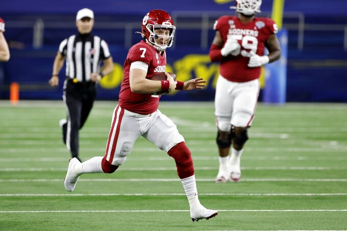 Oklahoma's Spencer Rattler (7) keeps the ball for a long gain in the second half of the team's Cotton Bowl NCAA college football game against Florida in Arlington, Texas, Wednesday, Dec. 30, 2020. (AP Photo/Michael Ainsworth)