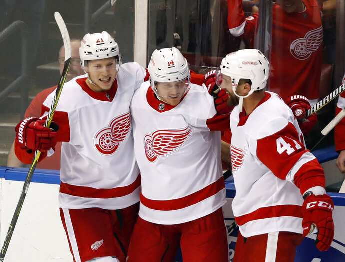 Detroit Red Wings right wing Gustav Nyquist, center, celebrates with defenseman Dennis Cholowski (21) and center Luke Glendening (41) after scoring the winning goal during an overtime period period of an NHL hockey game against the Florida Panthers, Saturday, Oct. 20, 2018, in Sunrise, Fla. The Red Wings defeated the Panthers 4-3 in overtime. (AP Photo/Wilfredo Lee)
