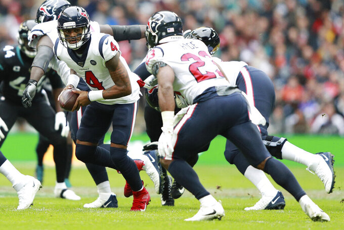 Houston Texans quarterback Deshaun Watson (4) prepares to hand the ball off to Houston Texans running back Carlos Hyde (23) against the Jacksonville Jaguars during the first half of an NFL football game at Wembley Stadium, Sunday, Nov. 3, 2019, in London. (AP Photo/Ian Walton)