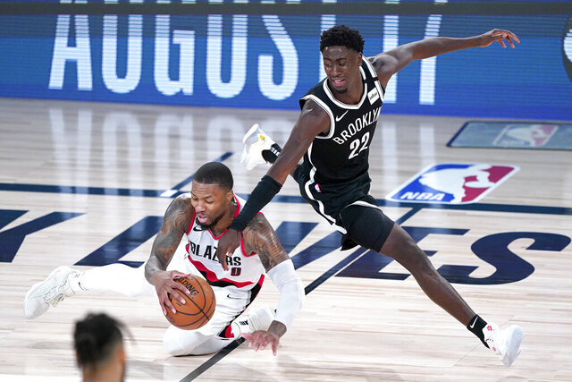 Portland Trail Blazers' Damian Lillard, left, falls while chasing the ball against Brooklyn Nets' Caris LeVert during the second half of an NBA basketball game Thursday, Aug. 13, 2020, in Lake Buena Vista, Fla. (AP Photo/Ashley Landis, Pool)