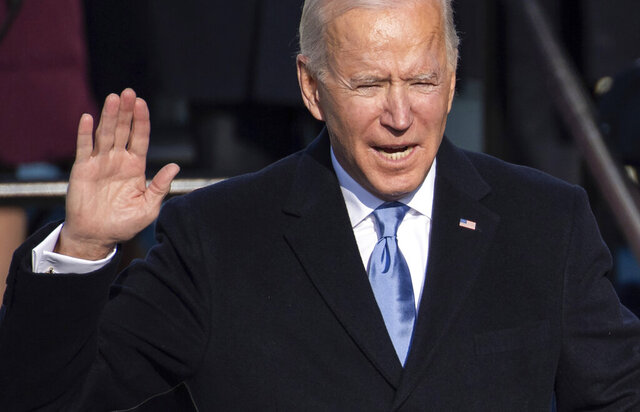 Joe Biden holds up his right hand as he is sworn in as the 46th president of the United States during the 59th Presidential Inauguration at the U.S. Capitol in Washington, Wednesday, Jan. 20, 2021. (Saul Loeb/Pool Photo via AP)