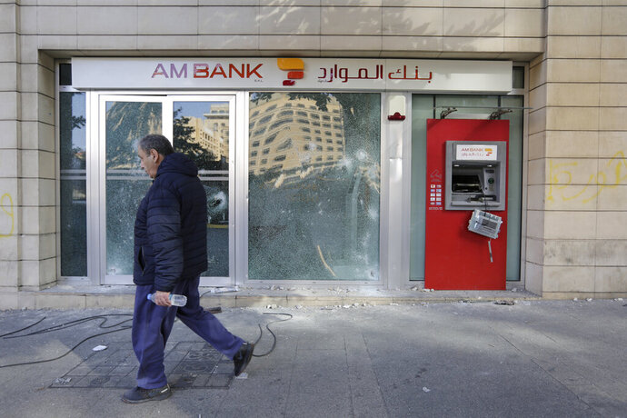 A man passes by an ATM machine damaged by protesters after a protest against the Lebanese government in Beirut, Lebanon, Saturday, Oct. 19, 2019. The blaze of protests was unleashed a day earlier when the government announced a slate of new proposed taxes, including a $6 monthly fee for using Whatsapp voice calls. The measures set a spark to long-smoldering anger against top leaders from the president and prime minister to the numerous factional figures many blame for decades of corruption and mismanagement. (AP Photo/Hassan Ammar)