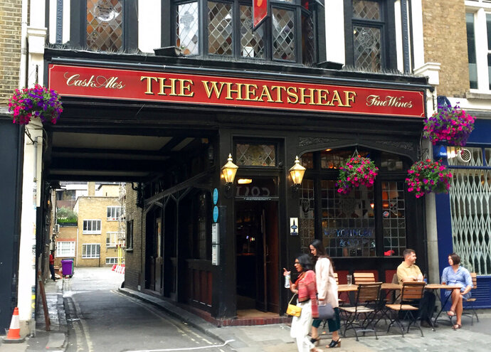 In this July 13, 2019, photo, tourists pass the Wheatsheaf pub in London, a spot where novelist George Orwell often visited. The London Literary Pub Crawl allows visitors to experience a playful and IPA-fueled tour unlocks stories linked to London locations where renowned novelists and poets drank and debated literature. (AP Photo/Russell Contreras)