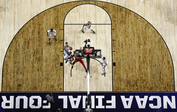 Michigan State's Kenny Goins (25), Nick Ward (44) and Texas Tech's Norense Odiase battle for a rebound during the first half in the semifinals of the Final Four NCAA college basketball tournament, Saturday, April 6, 2019, in Minneapolis. (AP Photo/Jeff Roberson)