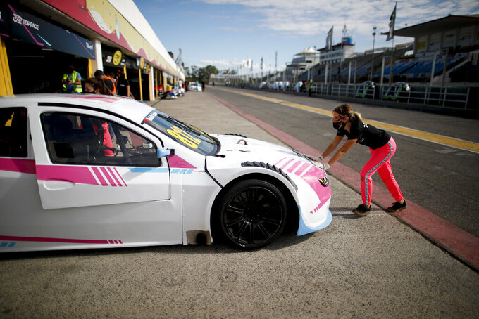 Vitarti Girl's Team mechanic Victoria Pascual pushes one of her team's racing cars into pits after a practice session at the Oscar y Juan Galvez track in Buenos Aires, Argentina, Friday, April 2, 2021. The Vitarti Girl's Team is the first all-female team in Argentina's motorsport history. (AP Photo/Natacha Pisarenko)