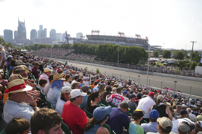 Fans watch the from the grandstands during the IndyCar Music City Grand Prix auto race Sunday, Aug. 8, 2021, in Nashville, Tenn. (AP Photo/Harrison McClary)