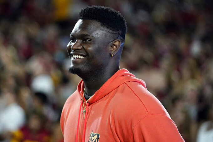 New Orleans Pelicans' Zion Williamson watches from the sideline during the first half of an NCAA college football game between Southern California and Stanford on Saturday, Sept. 11, 2021, in Los Angeles. (AP Photo/Marcio Jose Sanchez)