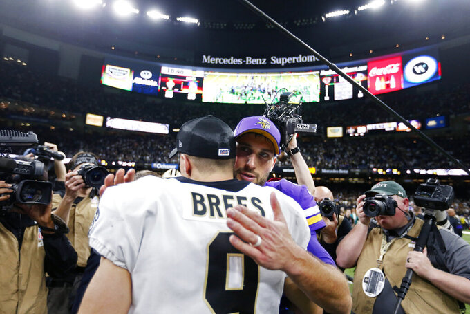 Minnesota Vikings quarterback Kirk Cousins hugs New Orleans Saints quarterback Drew Brees (9) after overtime of an NFL wild-card playoff football game, Sunday, Jan. 5, 2020, in New Orleans. The Vikings won 26-20. (AP Photo/Butch Dill)