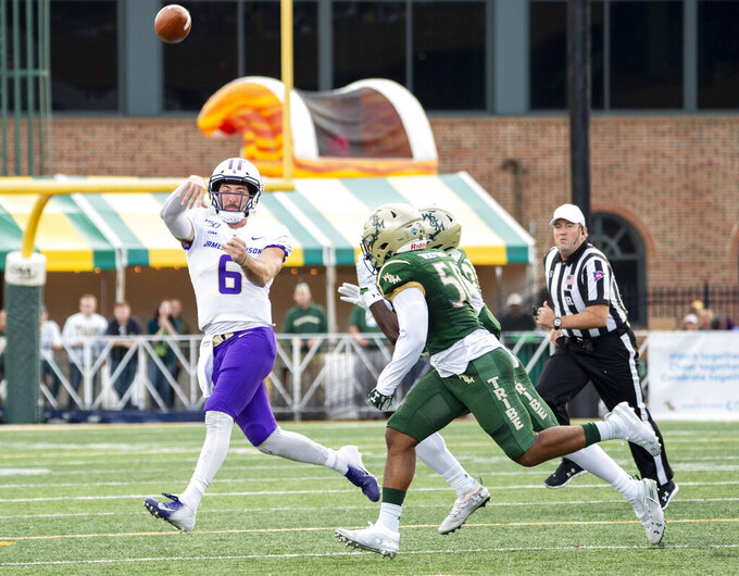 James Madison quarterback Ben DiNucci (6) is rushed out of the pocket by William & Mary linebackers Trey Watkins (50) and Atman Jones (21) during an NCAA college football game in Williamsburg, Va., on Saturday, Oct. 19, 2019. (Mike Caudill/The Virginian-Pilot via AP)