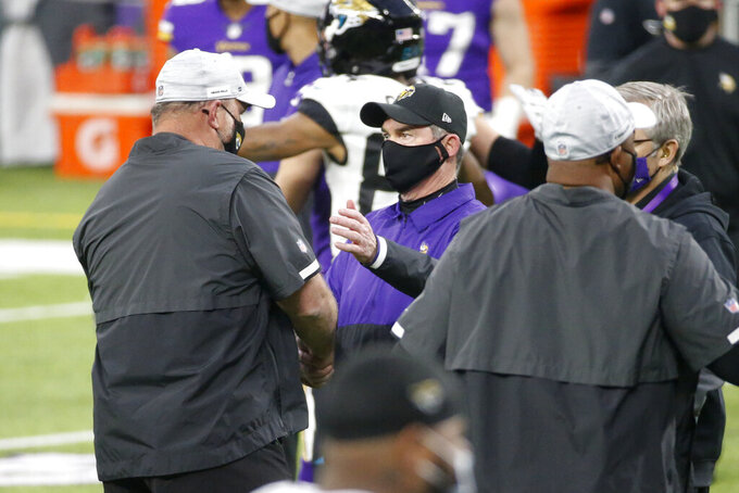 Minnesota Vikings head coach Mike Zimmer, center, greets Jacksonville Jaguars head coach Doug Marrone, left, after an NFL football game, Sunday, Dec. 6, 2020, in Minneapolis. The Vikings won 27-24 in overtime. (AP Photo/Bruce Kluckhohn)