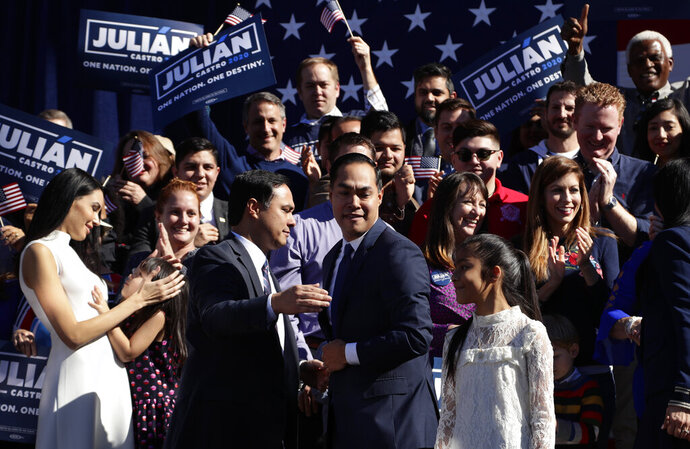 Former San Antonio Mayor and Housing and Urban Development Secretary Julian Castro, center right, is embraced by his twin brother U.S. Rep. Joaquin Castro (D-San Antonio), center left, during an event where Julian Castro announced his decision to seek the 2020 Democratic presidential nomination, Saturday, Jan. 12, 2019, in San Antonio. (AP Photo/Eric Gay)