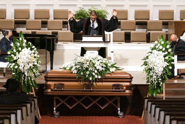 Pastor Richard W. Wills, Sr. prays during the funeral services for Henry