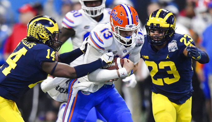 Florida quarterback Feleipe Franks (13) runs out of the pocket against Michigan defensive back Josh Metellus (14) during the first half of the Peach Bowl NCAA college football game, Saturday, Dec. 29, 2018, in Atlanta. (AP Photo/Mike Stewart)