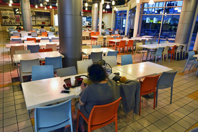In this Thursday, Feb. 27, 2020 photo, a customer eats a bowl of soup at a deserted food court in the Koreatown section of Los Angeles. Fears of the coronavirus combined with the speed and reach of social media can quickly cripple the healthiest of businesses. That's what happened to several Korean restaurants in Los Angeles. Their business was hit hard by false rumors spread on social media that a Korean Air flight attendant with coronavirus dined there last week. (AP Photo/Richard Vogel)