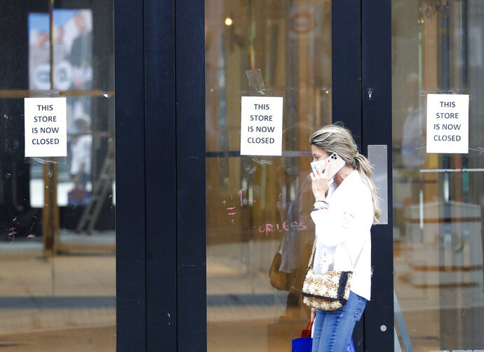 A woman walks by a closed store, in London, Thursday, July 16, 2020. Unemployment across the U.K. has held steady during the coronavirus lockdown as a result of a government salary support scheme, but there are clear signals emerging that job losses will skyrocket over coming months. The Office for National Statistics said Thursday there were 649,000 fewer people, or 2.2%, on payroll in June when compared with March when the lockdown restrictions were imposed. (AP Photo/Alastair Grant)