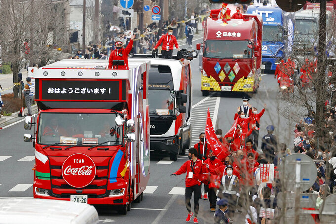 Olympic sponsors' vehicles parade ahead of torch relay on March 28, 2021, in Ashikaga, Tochigi prefecture, north of Tokyo. Now, nothing is certain as Tokyo's postponed Olympics hit the 100-days-to-go mark on Wednesday, April 14, 2021. (Shinji Kita/Kyodo News via AP)