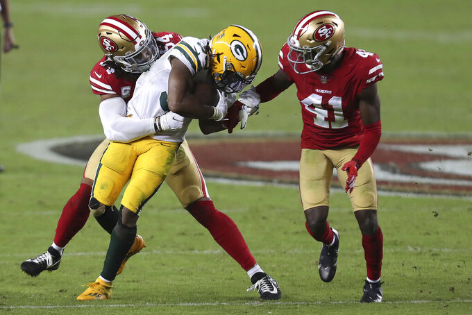 Green Bay Packers running back Aaron Jones, center, runs against San Francisco 49ers middle linebacker Fred Warner, left, and cornerback Emmanuel Moseley (41) during the second half of an NFL football game in Santa Clara, Calif., Thursday, Nov. 5, 2020. (AP Photo/Jed Jacobsohn)