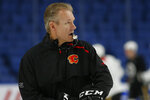 """Calgary Flames associate coach Geoff Ward gives instruction during an NHL hockey practice Tuesday, Nov. 26, 2019, in Buffalo, N.Y. Flames general manager Brad Treliving says coach Bill Peters remains on the staff but wasn't certain whether he'd be behind the bench for the next game. The team and the NHL are both investigating an allegation the Peters directed racial slurs at a player 10 years ago when the two were in the minors. Akim Aliu, a Nigerian-born player, says Peters """"dropped the N bomb several times"""" in a dressing room during his rookie year. (AP Photo/Jeffrey T. Barnes)"""