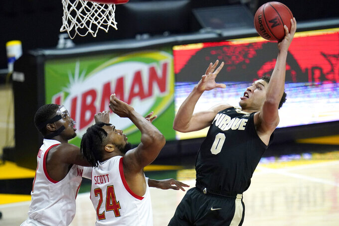Purdue forward Mason Gillis (0) goes up for a shot against Maryland forward Donta Scott (24) and guard Darryl Morsell during the first half of an NCAA college basketball game, Tuesday, Feb. 2, 2021, in College Park. (AP Photo/Julio Cortez)