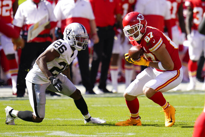 Kansas City Chiefs tight end Travis Kelce (87) catches a pass in front of Las Vegas Raiders cornerback Nevin Lawson (26) during the second half of an NFL football game, Sunday, Oct. 11, 2020, in Kansas City. (AP Photo/Jeff Roberson)