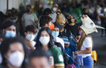 Young people, some wearing masks, wait to be vaccinated with a dose of the Pfizer COVID-19, during a vaccination drive for people between the ages of 18-29, in Mexico City, Thursday, Aug. 19, 2021. The capital's south side borough of Xochimilco is encouraging young residents to dress up in costumes and compete for prizes if they come for their first COVID-19 vaccine dose. (AP Photo/Eduardo Verdugo)