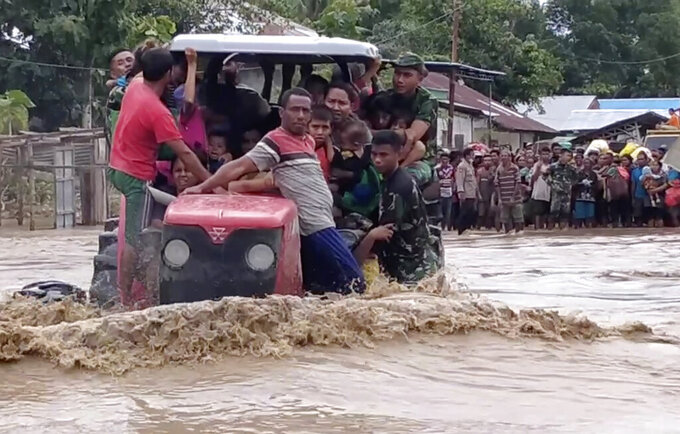 In this image made from video, Indonesian soldiers use a tractor to help residents to cross a flooded road in Malaka Tengah, East Nusa Tenggara province, Indonesia, Monday, April 5, 2021. Multiple disasters caused by torrential rains in eastern Indonesia have left dozens of people dead and missing and displaced thousands, the country's disaster relief agency said Monday. (AP Photo)