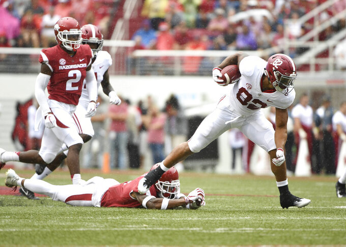 Alabama receiver Gary Cross slips past Arkansas defender Santos Ramirez in the first half of an NCAA college football game Saturday, Oct. 6, 2018, in Fayetteville, Ark. (AP Photo/Michael Woods)