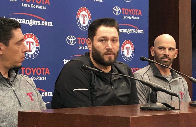 Newly signed Texas Rangers pitcher, Lance Lynn, center, responds to reporters questions as team general manager Jon Daniels, left, and manager Chris Woodward, right, look on in Arlington, Texas, Tuesday, Dec. 18, 2018. (AP Photo/Stephen Hawkins)
