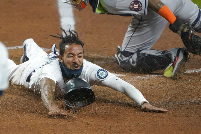 Seattle Mariners shortstop J.P. Crawford slides safely home past Houston Astros catcher Martin Maldonado during the fifth inning of a baseball game, Wednesday, Sept. 23, 2020, in Seattle. Crawford scored on a double hit by Kyle Seager. (AP Photo/Ted S. Warren)