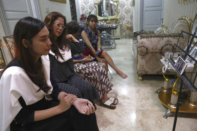 Fiance Tri Novia Septiani, left, and mother Herlina Simbala, second from left, of Dr. Michael Robert Marampe attend an online memorial service to mark the 40th day since Marampe passed away due to COVID-19 in Jakarta, Indonesia, on June 5, 2020. Marampe knew what he wanted to be since he was a kid: a doctor and a pianist. He became both, and his passion for music even led him to Septiani - a woman he never got to marry because he got the coronavirus. Marampe became one of dozens of doctors the coronavirus has claimed so far in Indonesia. (AP Photo/Tatan Syuflana)