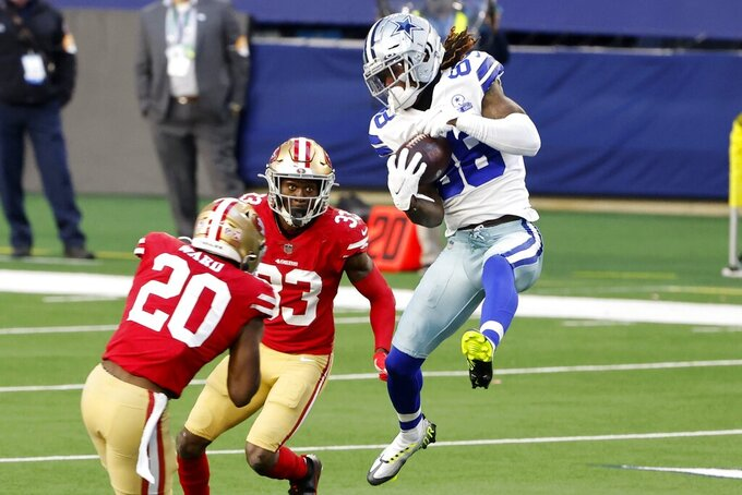 Dallas Cowboys wide receiver CeeDee Lamb (88) catches a pass between San Francisco 49ers' Jimmie Ward (20) and Tarvarius Moore (33) in the first half of an NFL football game in Arlington, Texas, Sunday, Dec. 20, 2020. (AP Photo/Michael Ainsworth)