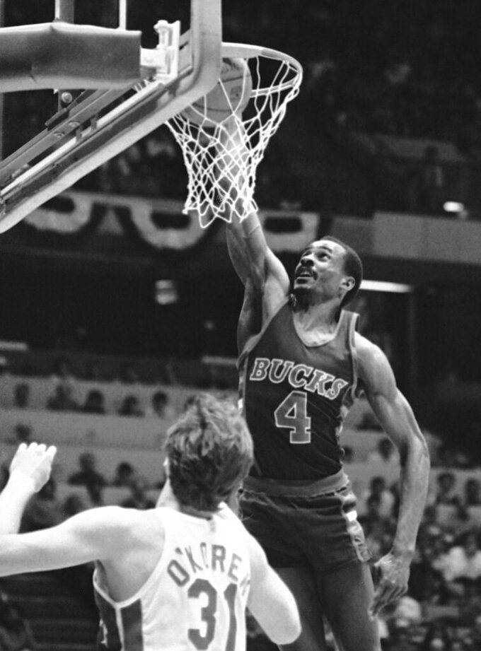 FILE - In this May 4, 1984, file photo, Milwaukee Bucks' Sidney Moncrief (4) drops in two of his game high 27 points over the New Jersey Nets' Mike OKoren during the first period an NBA playoff basketball game at Meadowlands Arena East Rutherford, N.J. NBA stars Vlade Divac, Sidney Moncrief and Jack Sikma are the headliners of the 2019 class for the Basketball Hall of Fame. The honorees were announced Saturday, April 6, 2019, in Minneapolis before the Final Four. (AP Photo/Ray Stubblebine, File)
