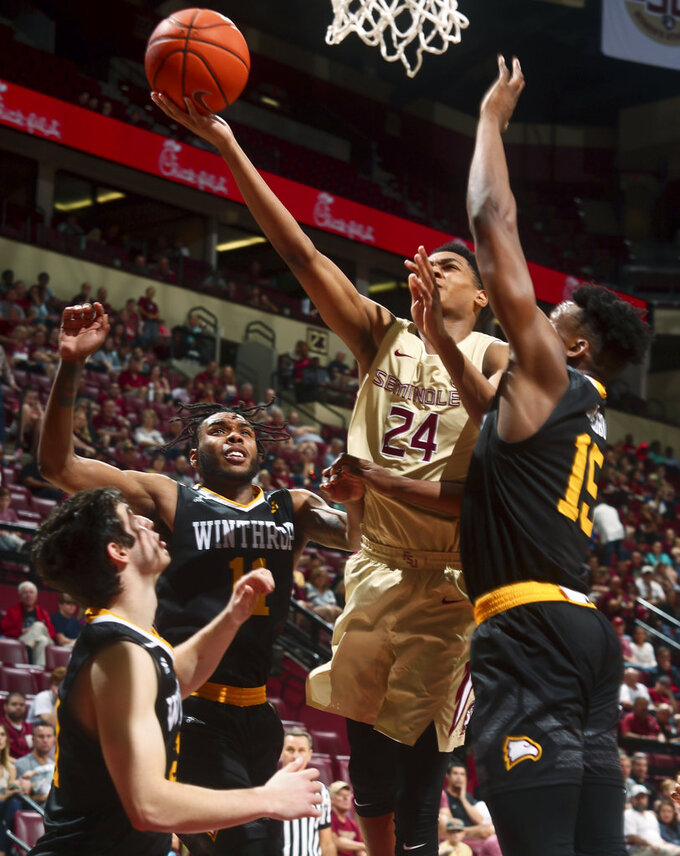 Florida State guard Devin Vassell (24) gets by Winthrop guard Charles Falden (11) and forward Jermaine Ukaegbu (15) for a layup in the second half of an NCAA college basketball game in Tallahassee, Fla., Tuesday, Jan. 1, 2019. Florida State won 87-76. (AP Photo/Phil Sears)