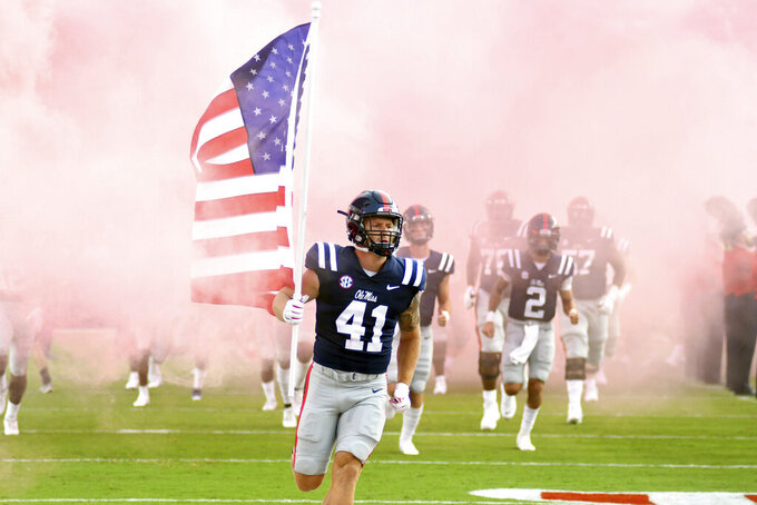 Mississippi's John Porchivina (41) carries a United States flag onto the field before an NCAA college football game against Austin Peay in Oxford, Miss., Saturday, Sept. 11, 2021. (AP Photo/Bruce Newman)