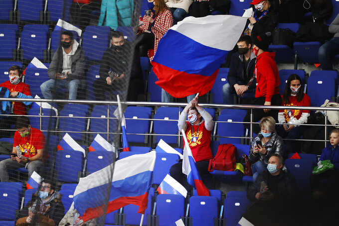 Russian spectators support their team during the Channel One Cup ice hockey match between Sweden and Russia in Moscow, Russia, Thursday, Dec. 17, 2020. The Court of Arbitration for Sport confirmed Russia's flag and anthem are barred from next year's Olympics in Tokyo and the 2022 Winter Games in Beijing on Thursday. (AP Photo/Pavel Golovkin)