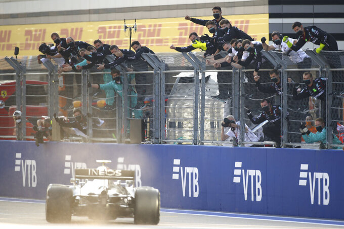 Team members cheer as Mercedes driver Valtteri Bottas of Finland steers his car to win the Russian Formula One Grand Prix, at the Sochi Autodrom circuit, in Sochi, Russia, Sunday, Sept. 27, 2020. (Bryn Lennon, Pool via AP)