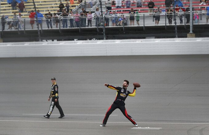Daniel Hemric, left, and Corey LaJoie play catch with race fans during a rain delay at the NASCAR cup series auto race at Michigan International Speedway, Sunday, June 9, 2019, in Brooklyn, Mich. The race has been rescheduled for Monday. (AP Photo/Carlos Osorio)