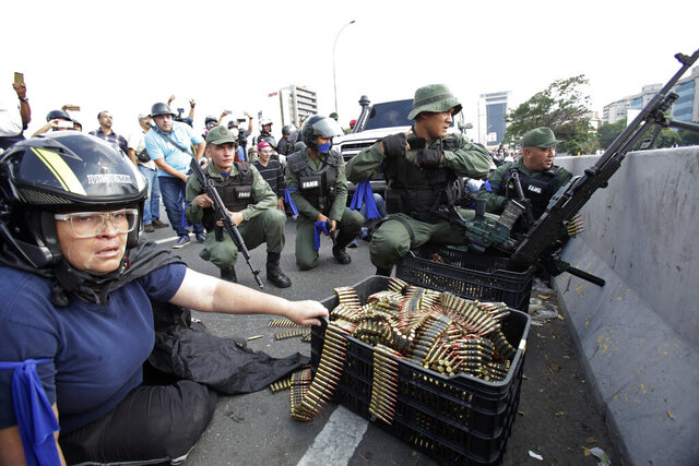 FILE - In this April 30, 2019 file photo, an anti-government protester sits by ammunition being used by rebel troops rising up against Venezuelan President Nicolas Maduro as they all take cover on an overpass outside La Carlota military air base where the rebel soldiers confront loyalist troops inside the base in Caracas, Venezuela. Contrary to what the Trump administration was promised at the time, key Maduro aides never joined with the opposition and the uprising was quickly quashed. (AP Photo/Boris Vergara, File)