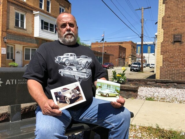 Todd Barbiaux, presiident of United Steelworkers Local 1196, holds pictures of two of the stainless steel Fords, a 1936 sedan and a 1967 Lincoln Continental, produced by Allegheny Ludlum outside the union hall in Brackenridge, Pa., on Tuesday, May 26, 2020. (Brian C. Rittmeyer/Tribune-Review via AP)