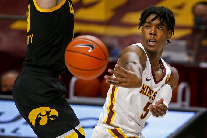 Minnesota guard Marcus Carr passes the ball around Iowa guard Joe Wieskamp, left, during the second half of an NCAA college basketball game Friday, Dec. 25, 2020, in Minneapolis. Minnesota won 102-95 in overtime. (AP Photo/Bruce Kluckhohn)