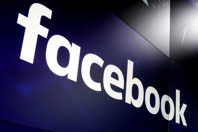 """FILE- In this March 29, 2018, file photo, the logo for Facebook appears on screens at the Nasdaq MarketSite in New York's Times Square. Days before Germany's federal elections, Facebook removed a network of accounts that it said had spread COVID-19 misinformation and encouraged violent responses to COVID restrictions. The crackdown, announced Sept. 16, 2021, was the first use of Facebook's new """"coordinated social harm"""" policy aimed at stopping not state-sponsored disinformation campaigns but otherwise typical users who have mounted an increasingly sophisticated effort to sidestep rules on hate speech or misinformation.  (AP Photo/Richard Drew, File)"""
